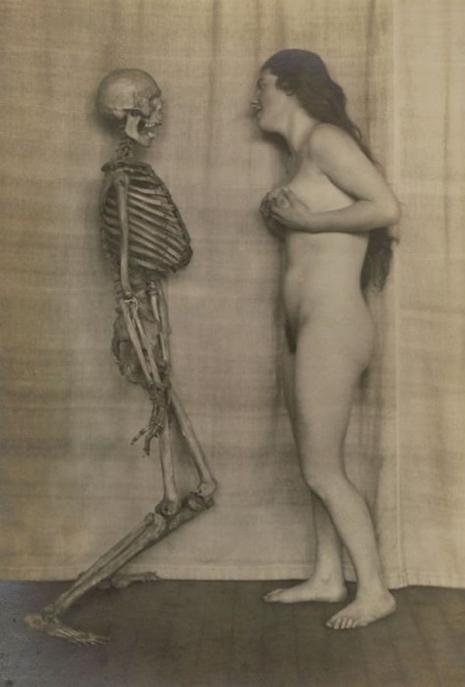 Naga kobieta stojąca naprzeciwko szkieletu
