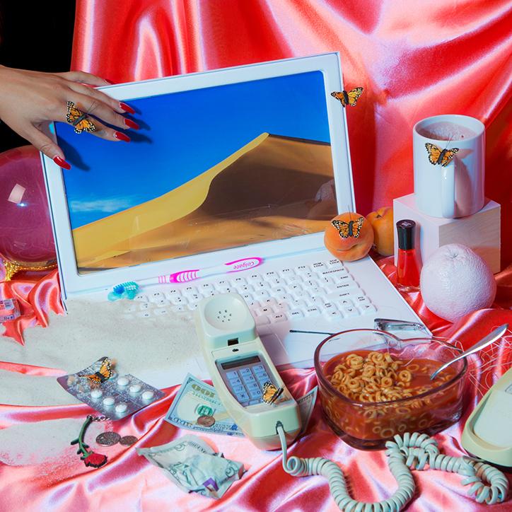 Porozkładane przedmioty: komputer, telefon, kubek, bibeloty na różowym kawałku satyny