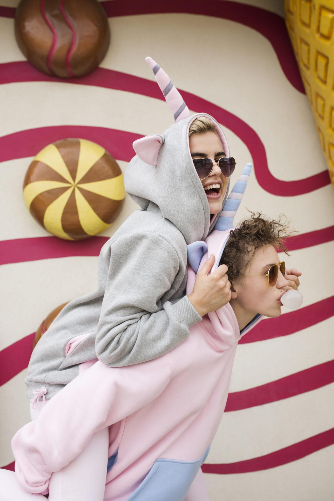 Dwie dziewczyny ubrane w bluzy - jednorożce na tle kolorowej ściany