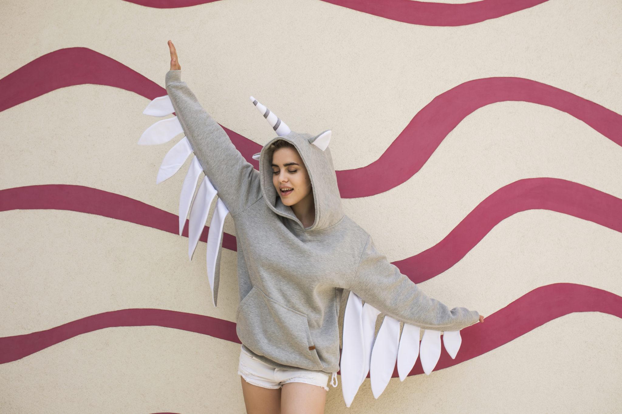 Dziewczna ubrana w bluzę z kapturem jednorożca, stojąca na tle kolorowej ściany