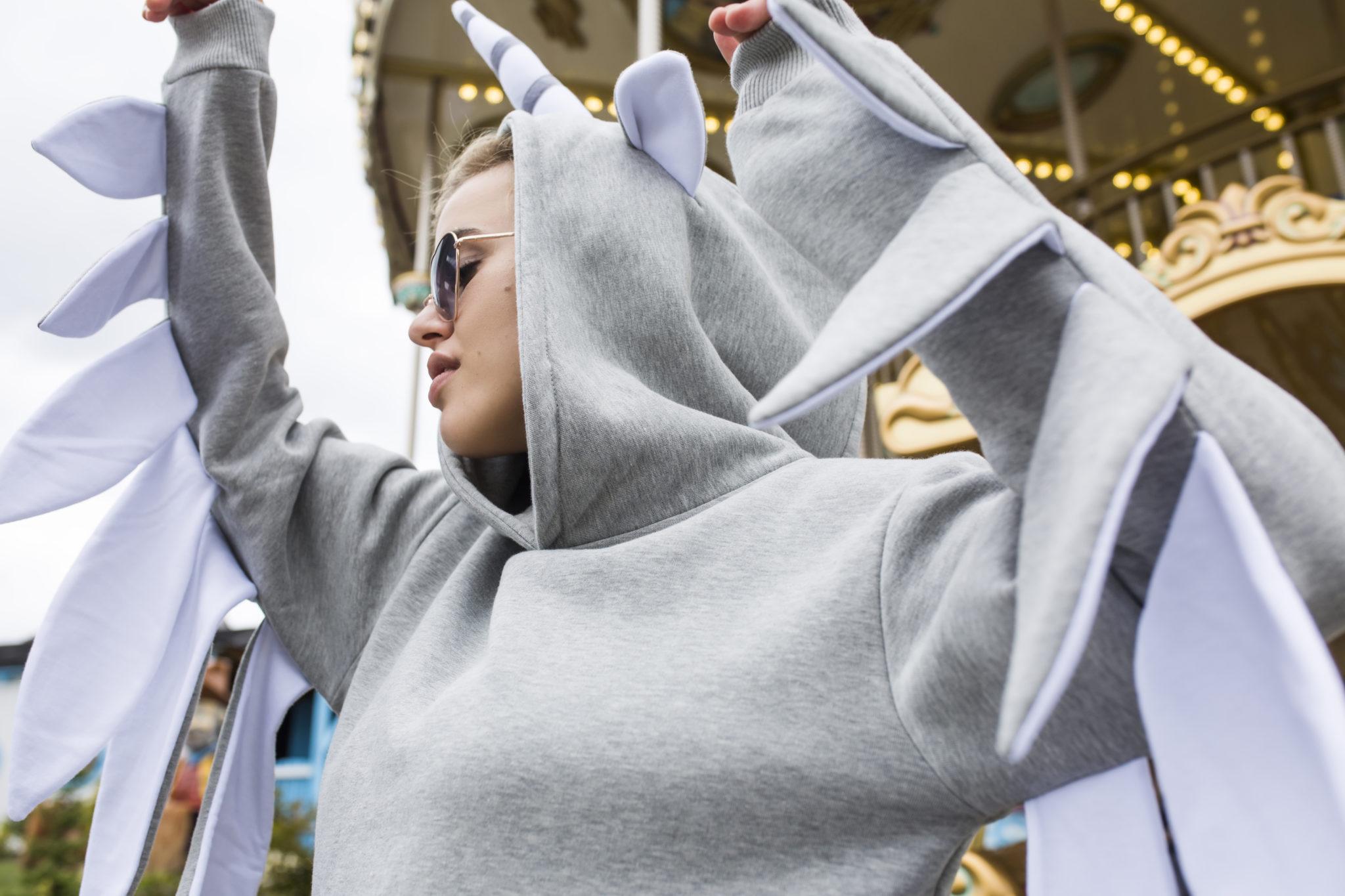 Dziewczyna w szarej bluzie z rogiem jednorożca na kapturze