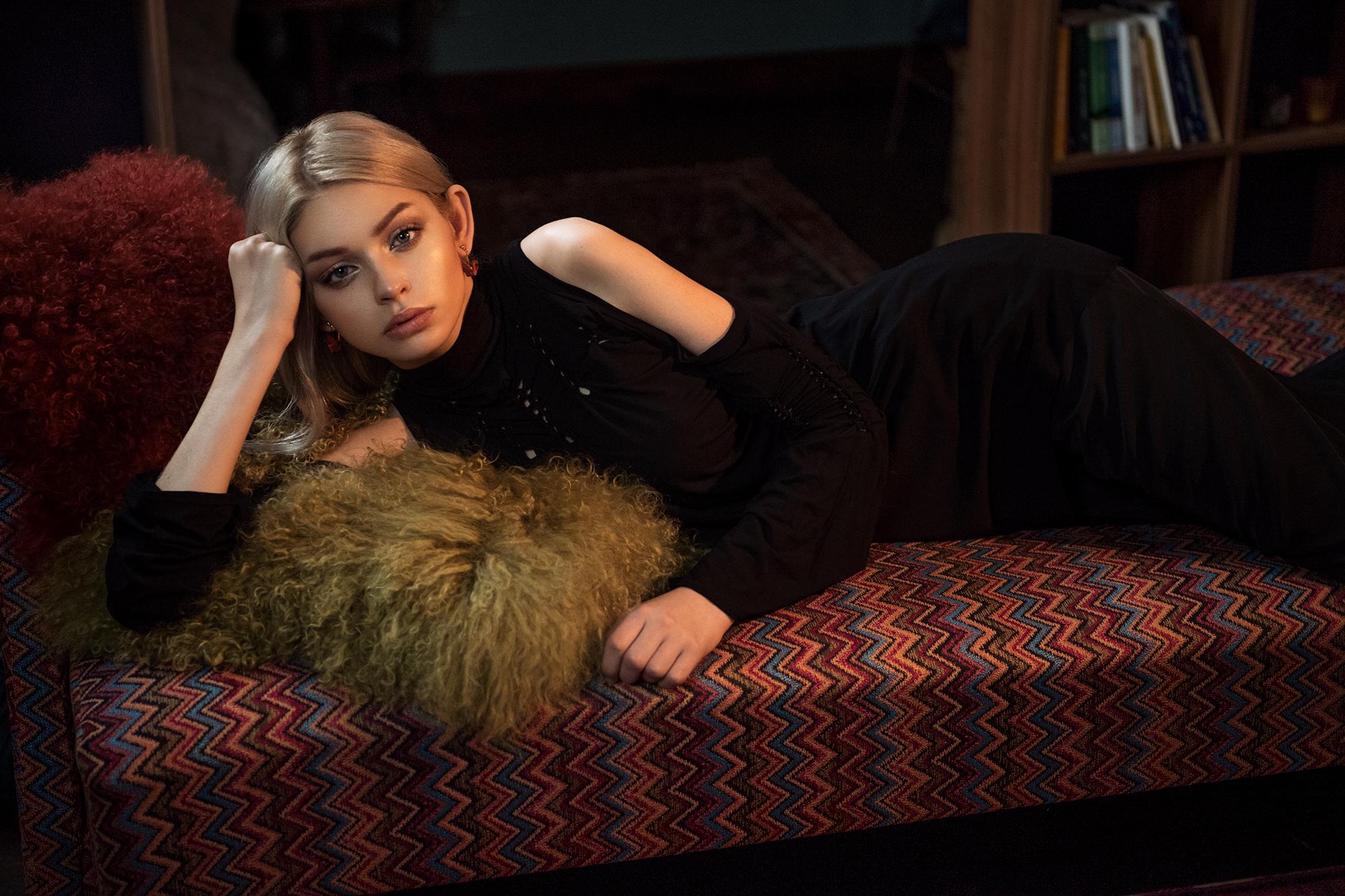 Dziewczyna leżąca na tapczanie, podpierająca głowę ręką z futrzastą poduszką pod ramieniem