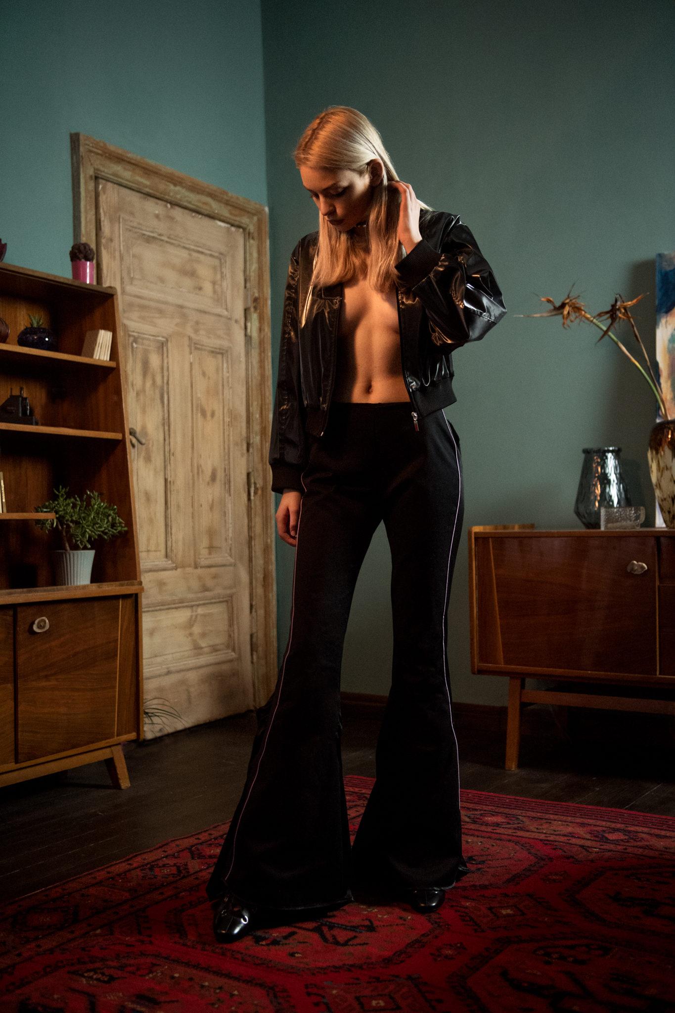 Dziewczyna w ciemnych spodniach typu dzwony stojąca w eklektycznym wnętrzu