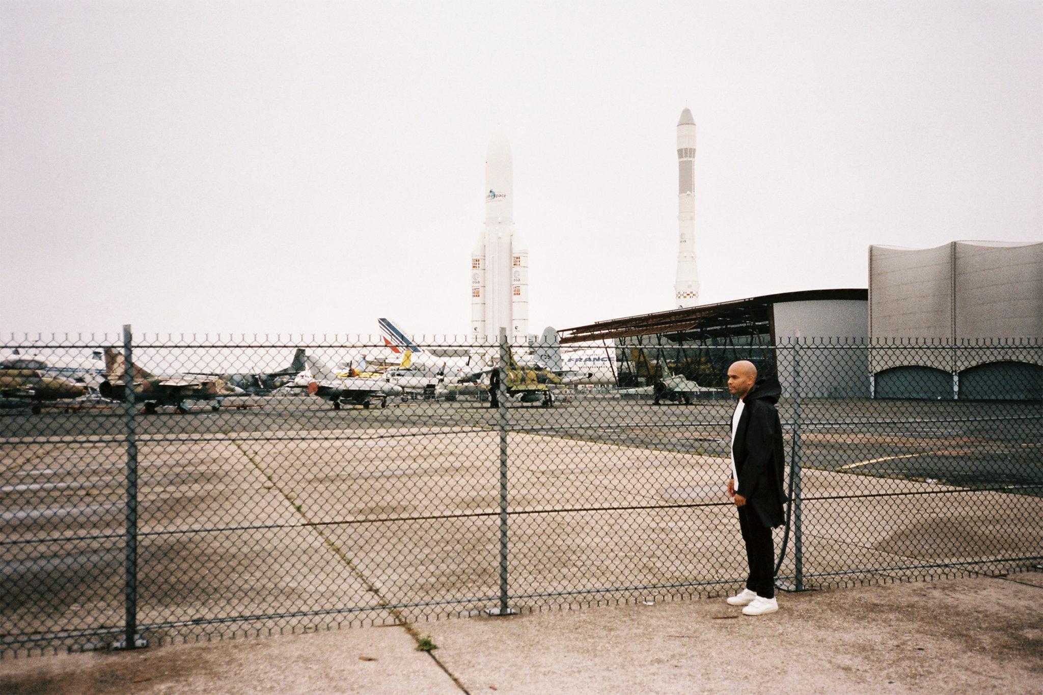Mężczyzna stojący przed ogrodzeniem lotniska