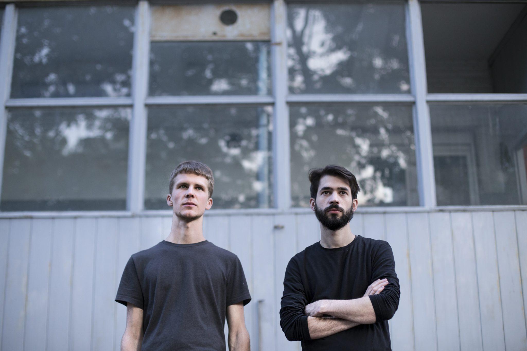 Dwóch mężczyzn stojących na tle budynku