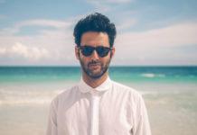 Mężczyzna w białej koszuli i okularach przeciwsłonecznych stojący na plaży, w tle morze