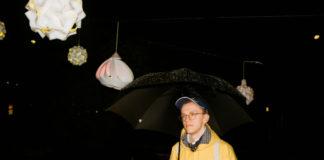 Biały chłopiec w żółtej kurtce z czapką, trzyma parasolkę podczas mocnej ulewy na tle lampionów.