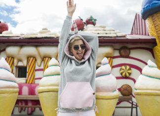 Dziewczyna ubrana w bluzę z kapturem jednorożca, stojąca na tle kolorowego samochodu