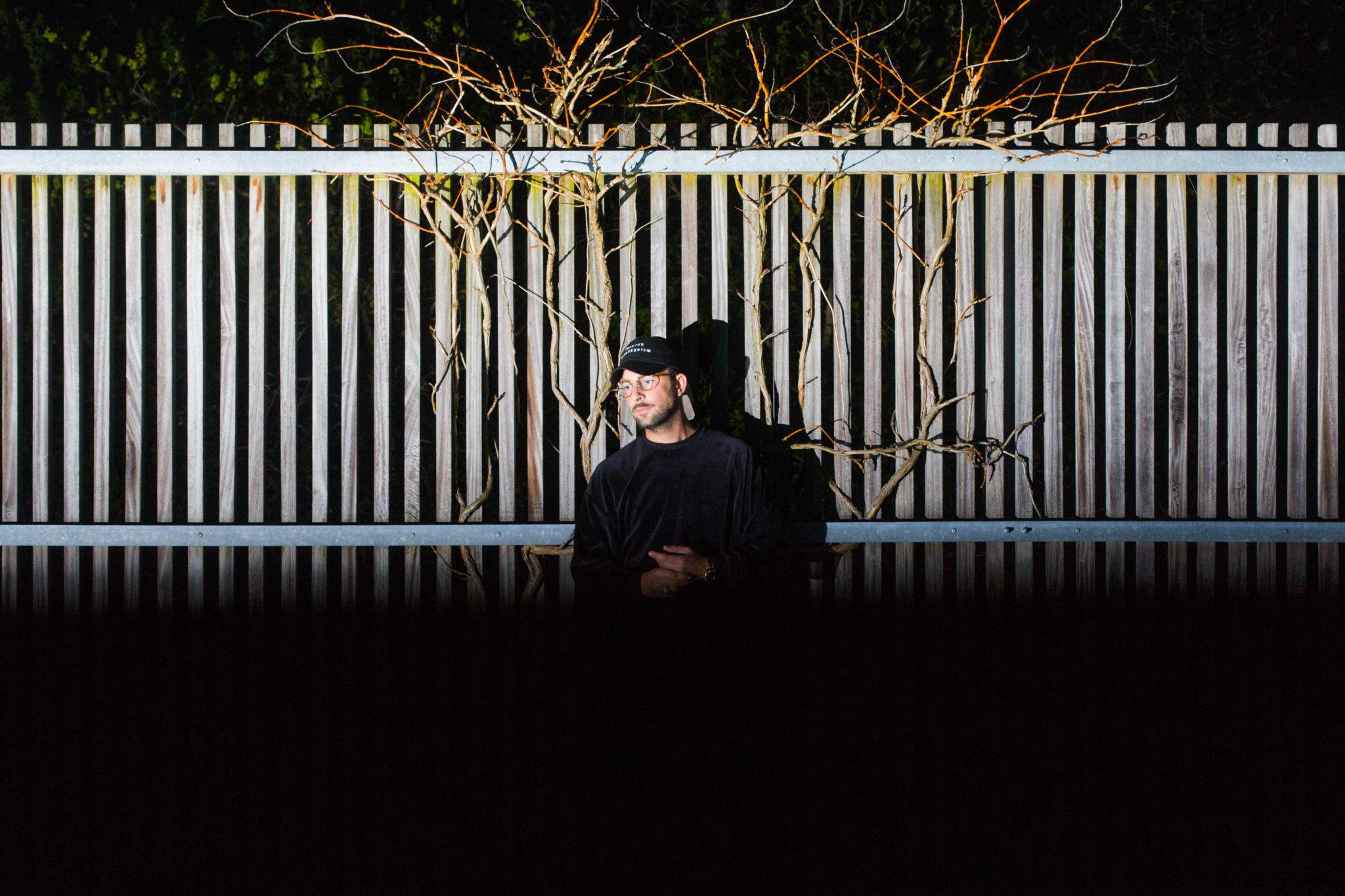 Mężczyzna w ciemności na tle białego płota