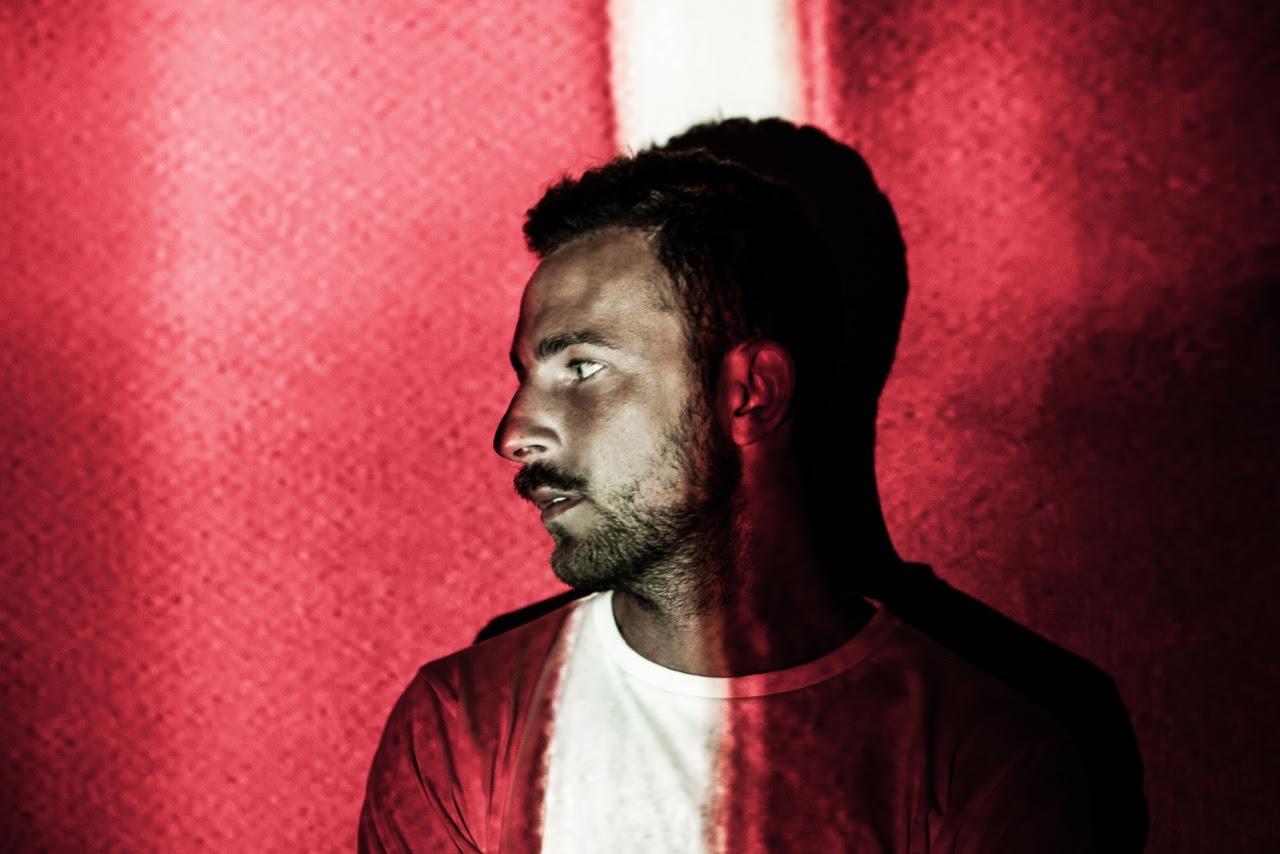 Mężczyzna oparty na ścianę, z czerwonym światłem na twarzy
