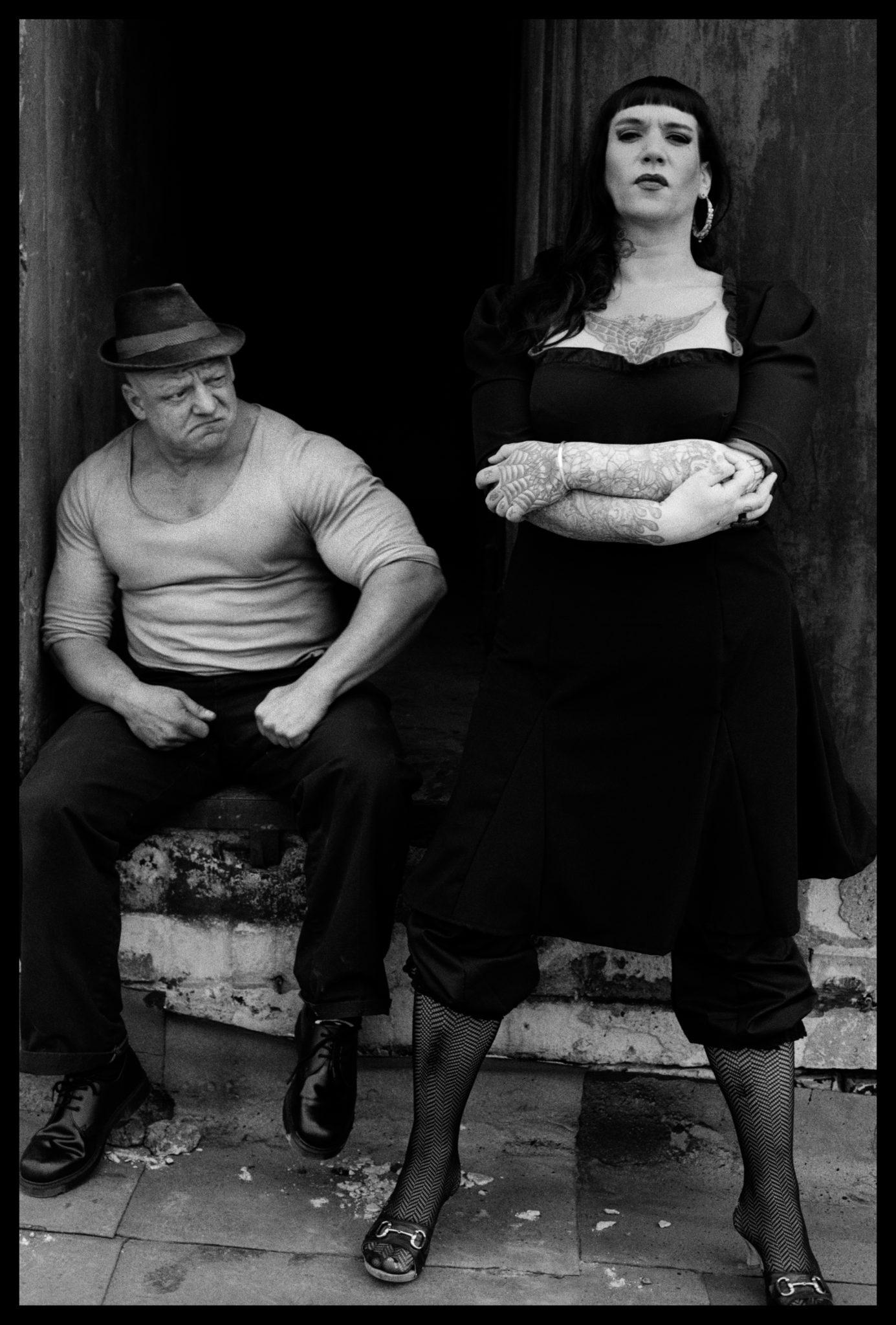 Czarno-białe zdjęcie mężczyzny siedzącego na schodku i kobiety w czarnej sukience stojącej obok niego