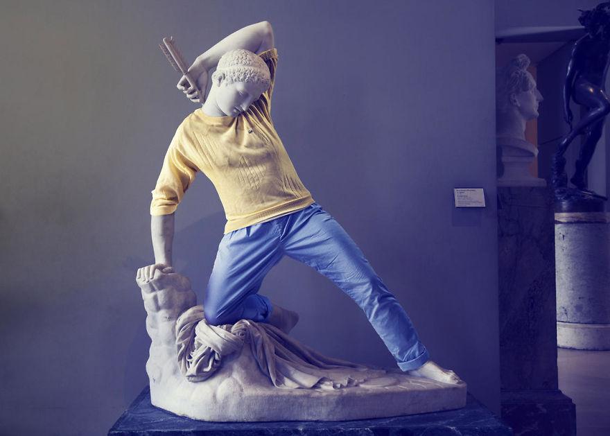 Klasyczna rzeźba ubrana w jeansy i żółty sweter
