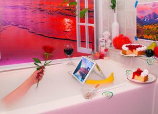 Surrealistyczne zdjęcie z wanną z widokiem na plażę, tabletem, dłonią trzymająca różę, ciastem, winem, papierosem