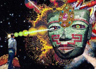 Człowiek w czarnej pustce. Z jego głowy wychodzi świetlny promień łączący z wielką twarzą stworzoną z kształtów geometrycznych.