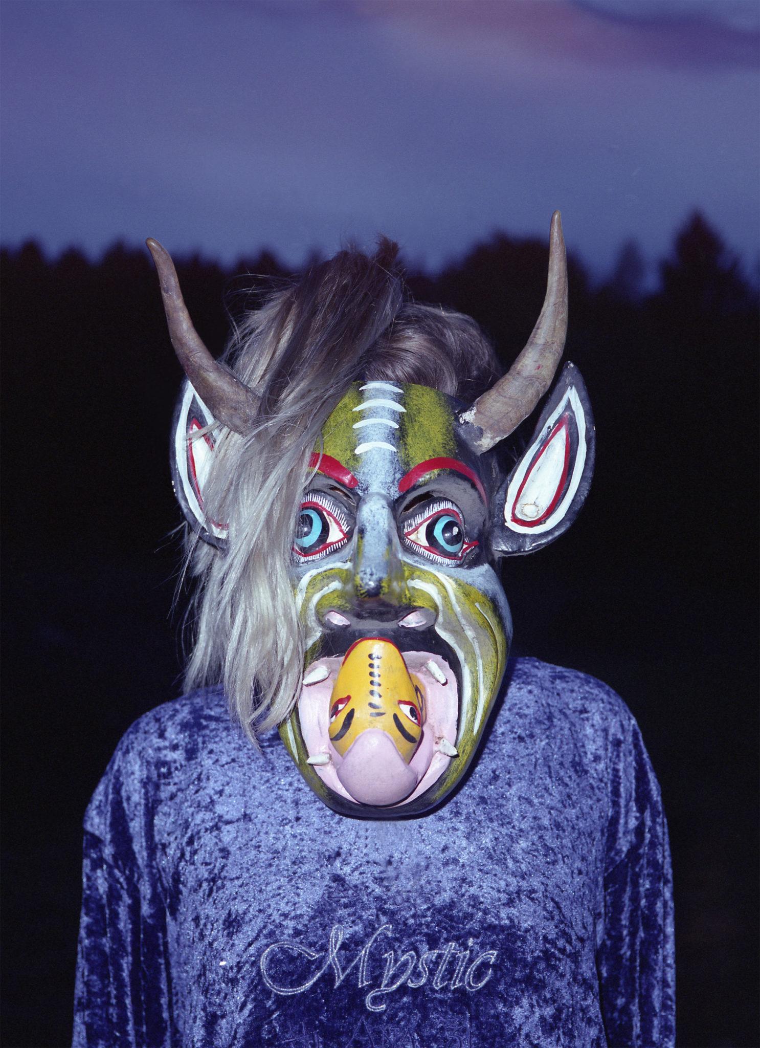 """Postać ubrana w bluzę z napisem ,,Mystic"""", oprócz niej ma też na sobie maskę. Maska jest hybrydą kilku rzeczy czy zwierząt, tj. wąż, rogi."""