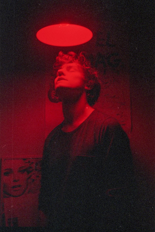 Mężczyzna ma skierowaną głowę w stronę lampy, która jest nad nim. Ma zamknięte oczy.