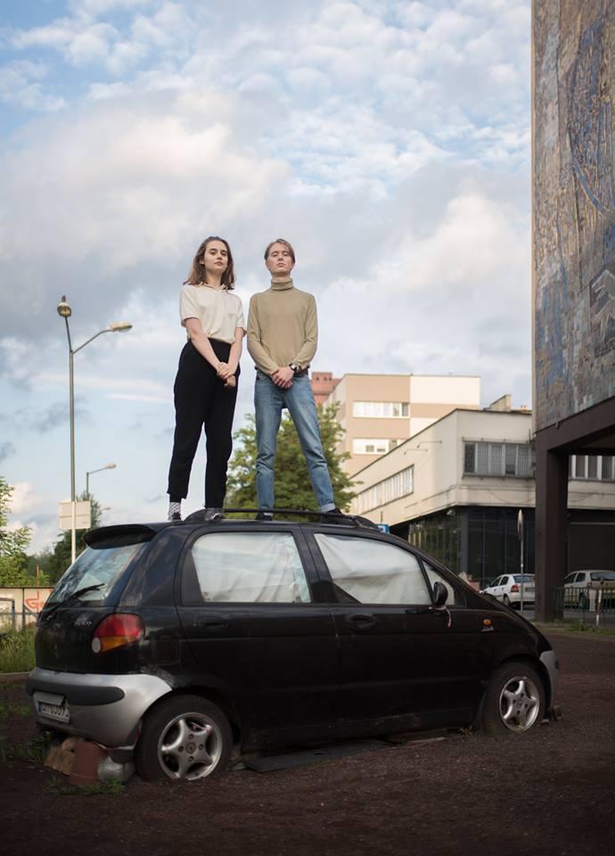 Chłopak i dziewczyna stojący na dachu samochodu