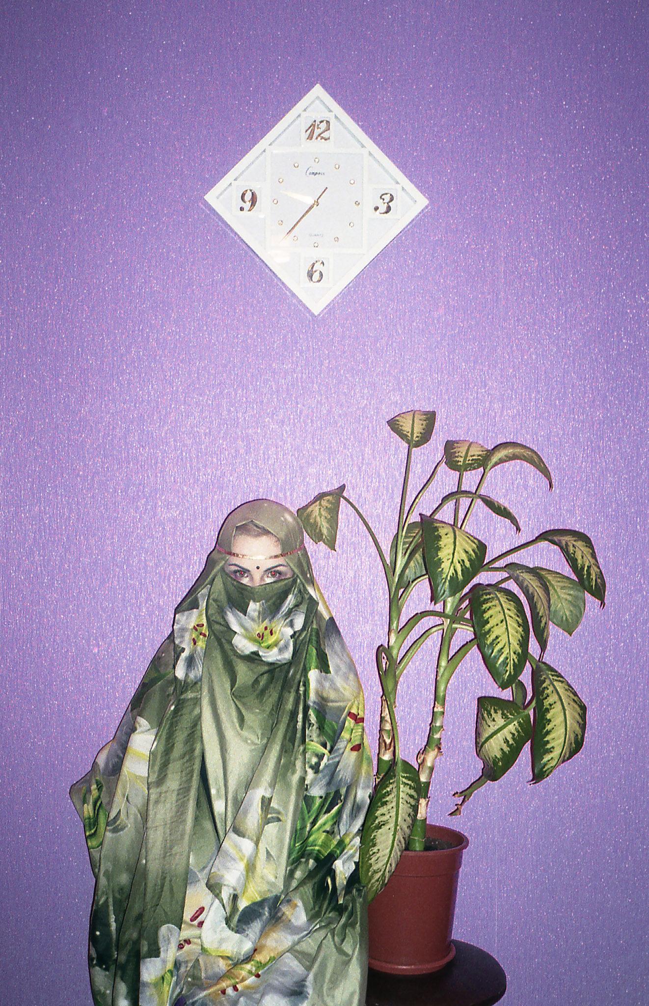 Młoda kobieta stoi ubrana w burce z kwiatami. Przy niej stoi roślina w doniczce, a nad nią znajduję się zegar w kształcie kwadratu.