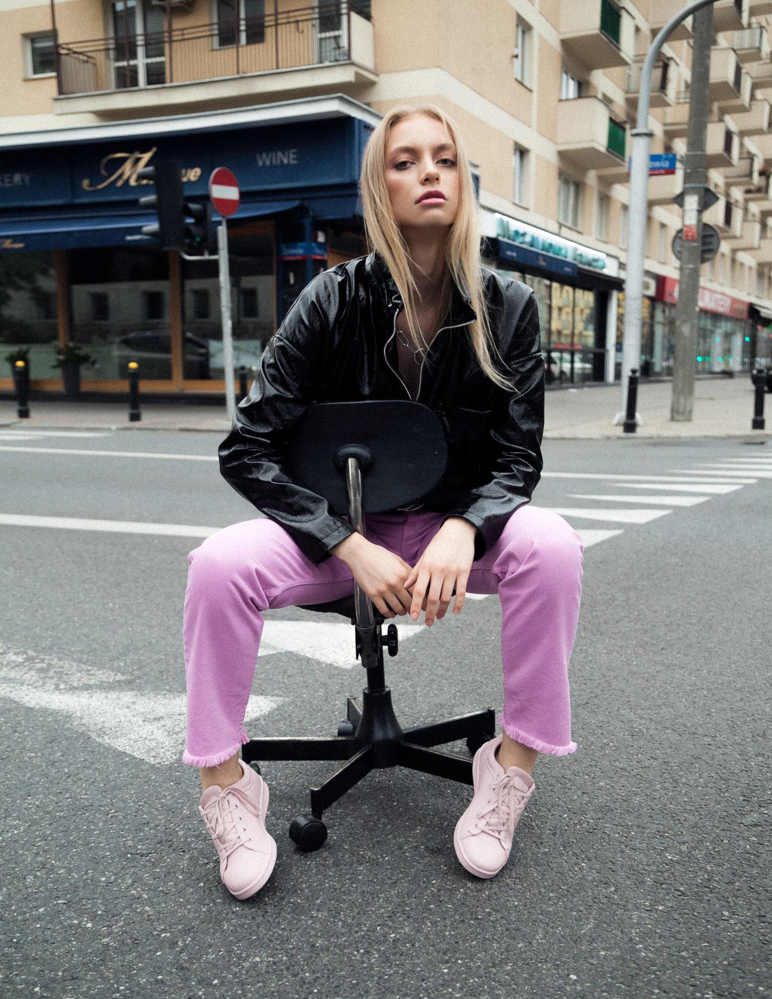 Dziewczyna w różowych spodniach i czarnej kurtce siedzi na środku ulicy na krześle z kółkami