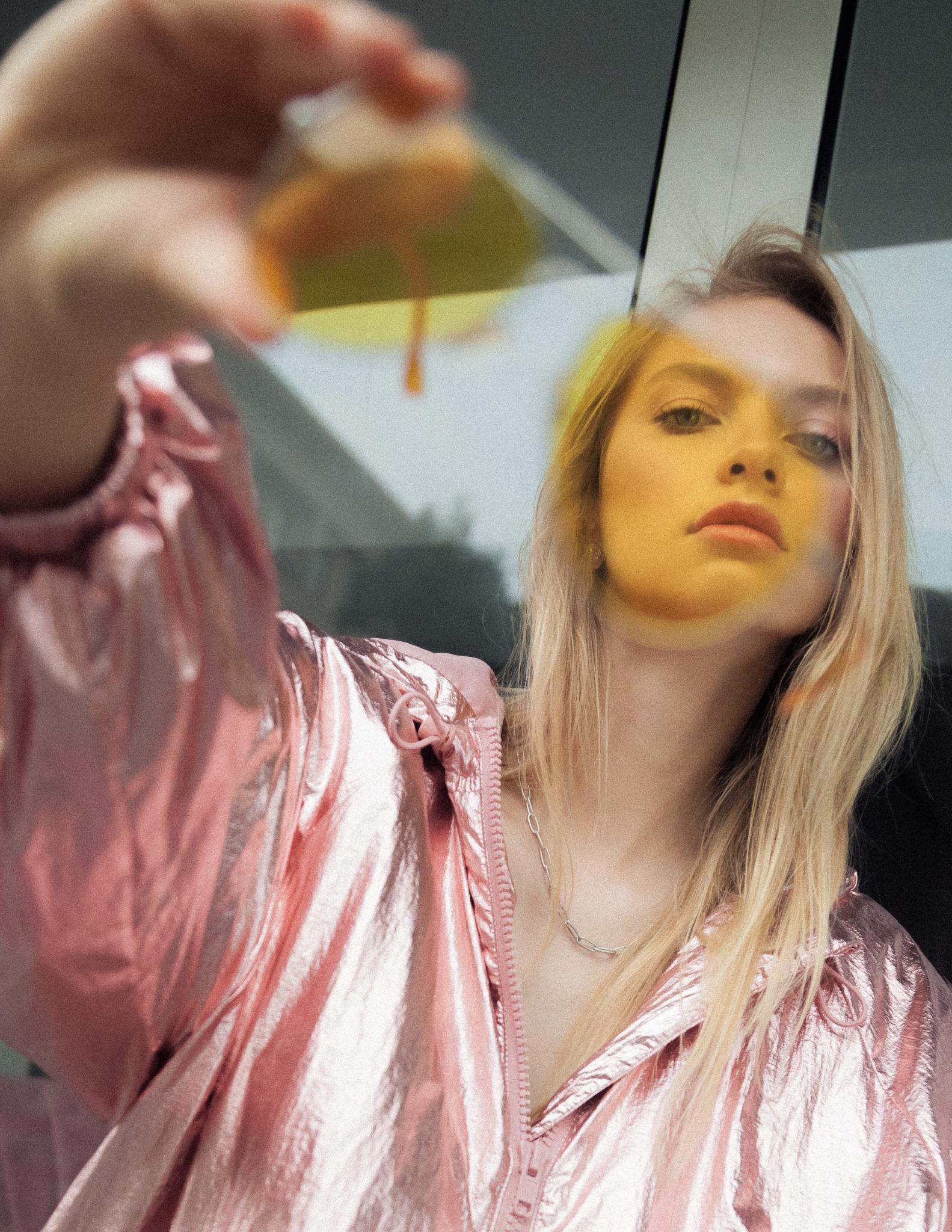 Dziewczyna w różowej kurtce trzyma przed obiektywem kamery okulary przeciwsłoneczne
