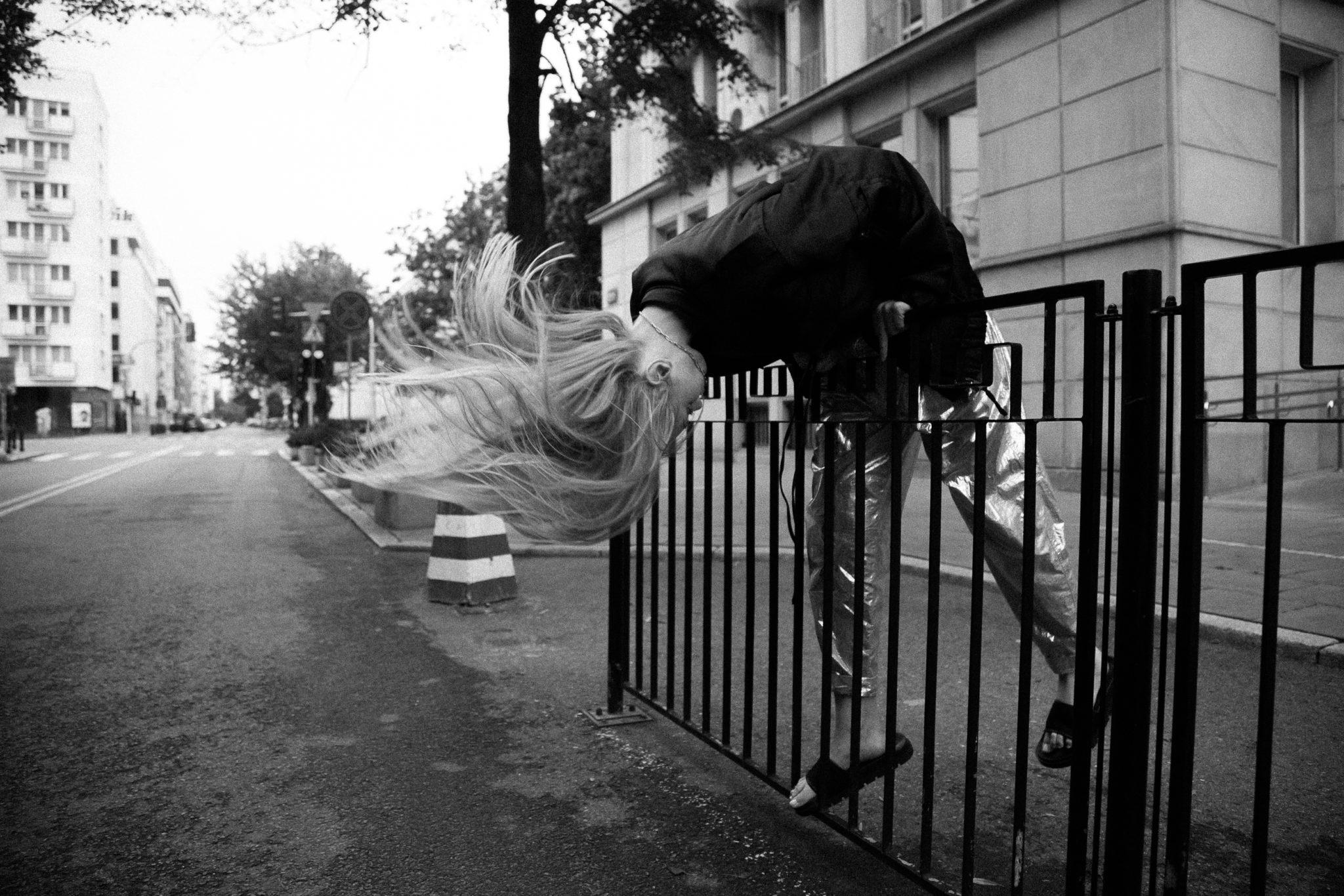 Czarno-białe zdjęcie dziewczyny przechylającej się przez barierkę