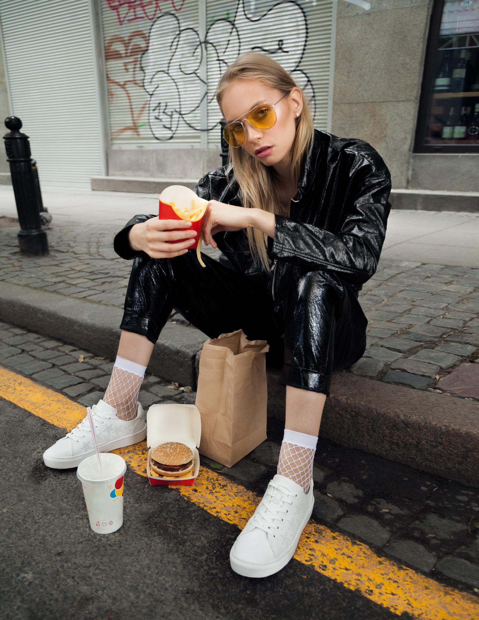 Dziewczyna w czarnych spodniach i kurce z białymi butatmi i przezroczystymi skarpetami siedzi na kraweżniku z frytkami w ręku