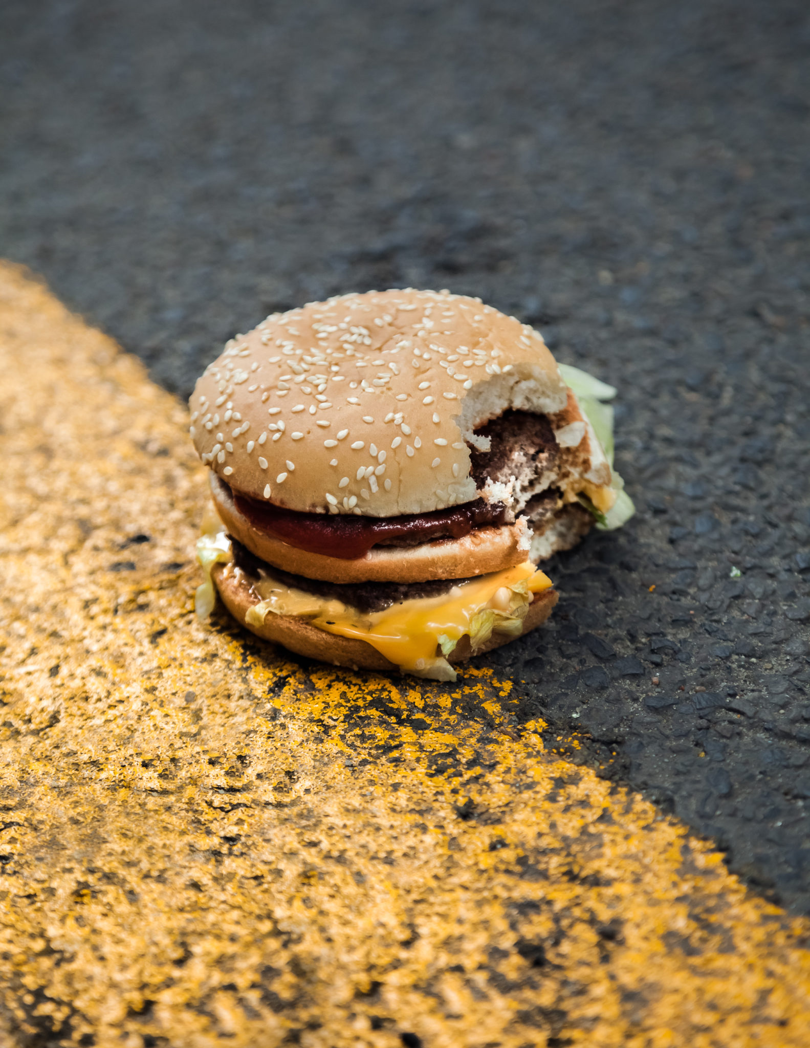 Nadgryziony hamburger leżący na jezdni