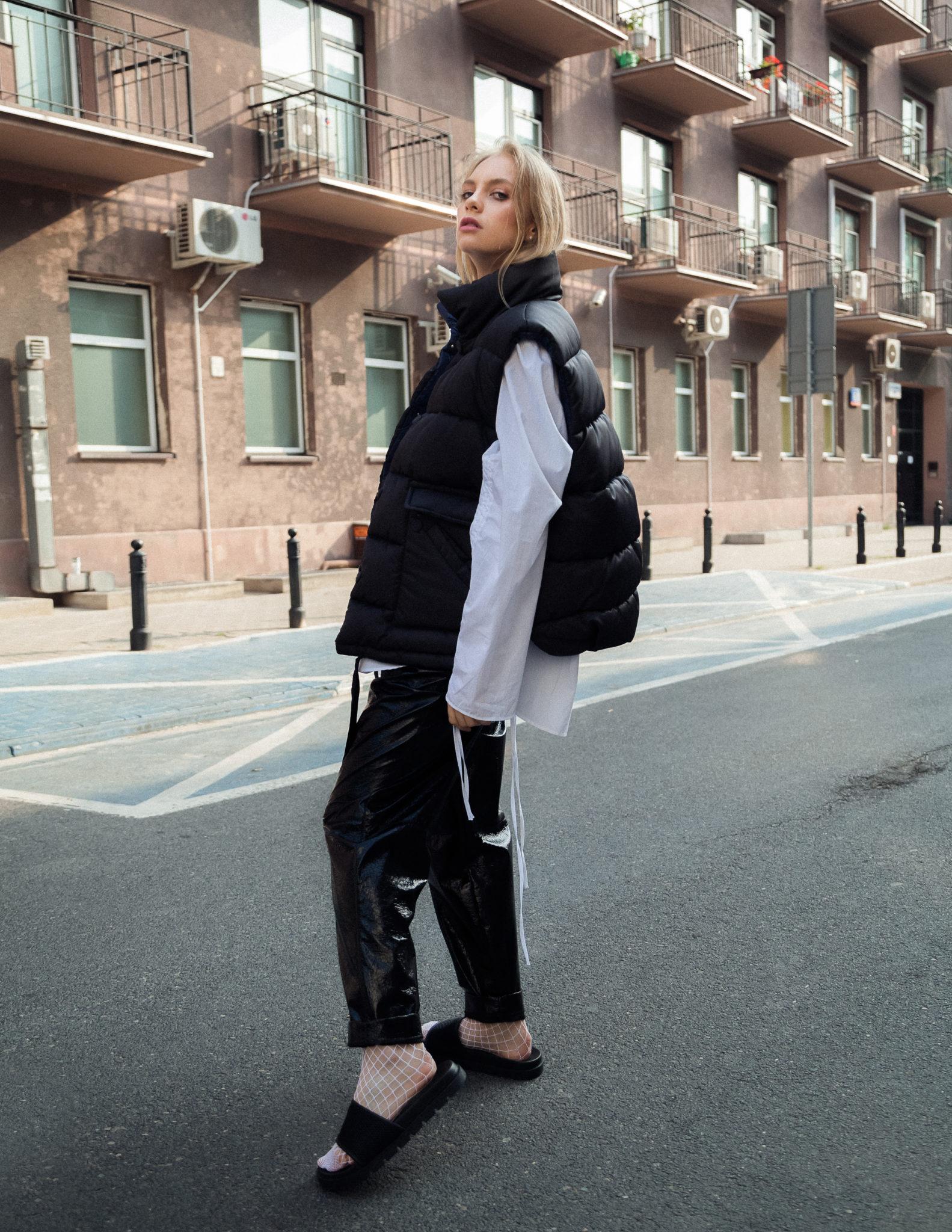Dziewczyna w czarnych spodniach i puchowej kamizelce stojąca na środku ulicy