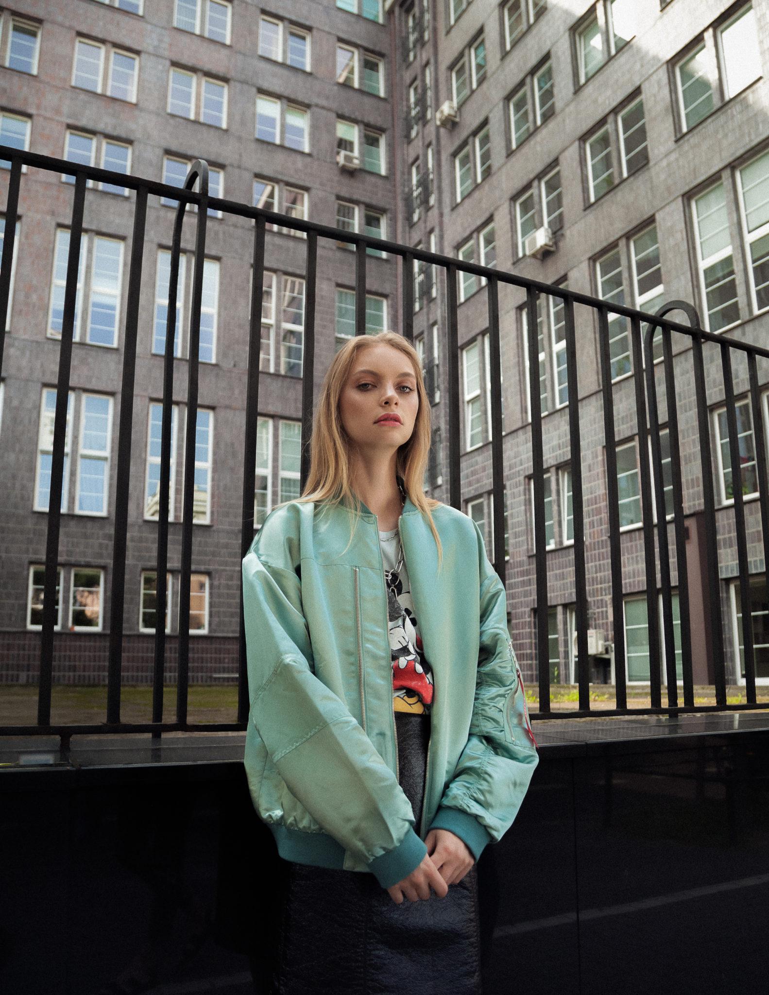 Dziewczyna oparta o kraty ogrodzenia, ubrana w miętową kurtkę typu bomberka