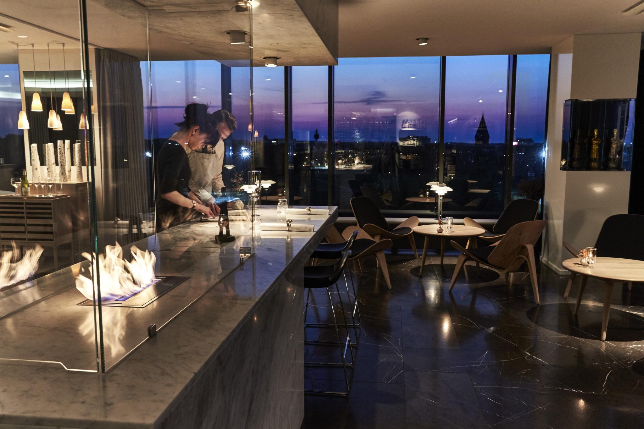 Ekskluzywne wnętrze restauracji o zmroku. W tle miejski krajobraz za oknem
