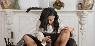 młoda kobieta siedząca na stołku z rozłożonymi nogami obserwująca w lusterku swoje nagie ciało