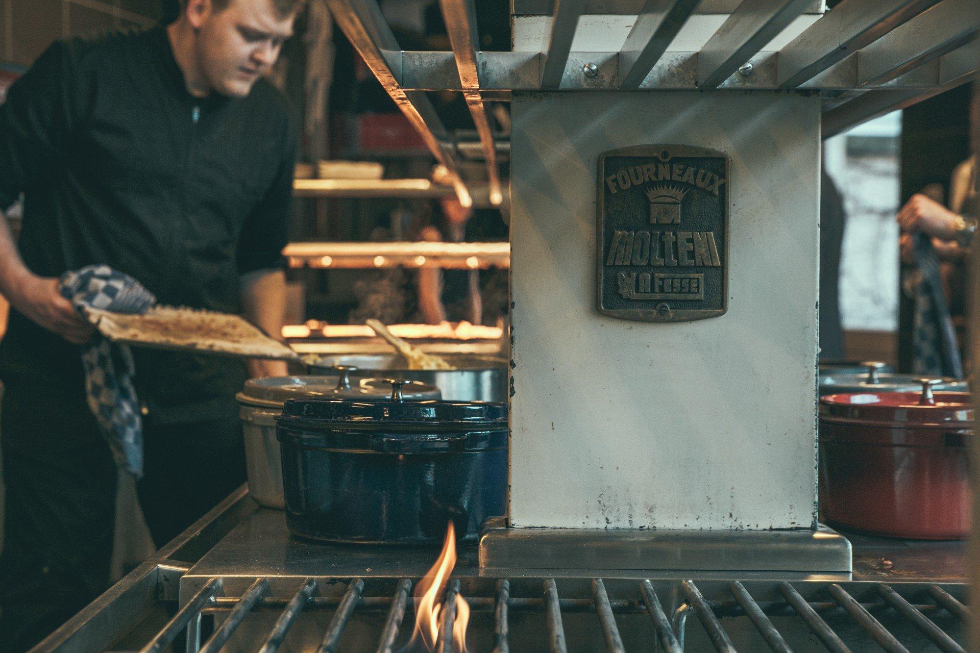 Kucharz wkłada blachę do pieca kamiennego