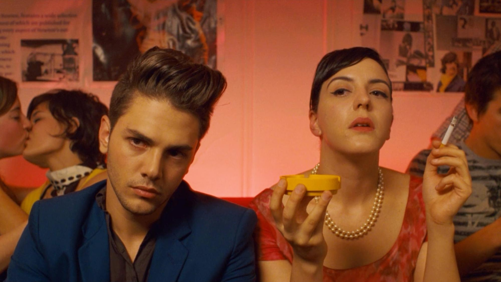 Kobieta i mężczyzna siedzą podczas imprezy, ona pali papierosa, on patrzy się pogardliwym wzrokiem.