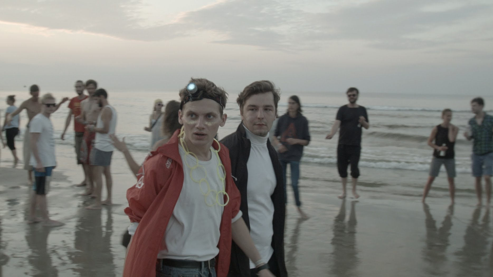Dwójka młodych ludzi idzie przez plażę nad wczesnym ranem podczas imprezy.