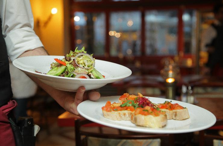 Wnętrze restauracji i ręka kelnera serwującego dwa dania