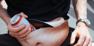 Nerka z nadrukowanym męskim, owłosionym brzuchem, do któej mężczyzna wkłąda piwo w puszce