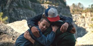 """Kadr z serialu ,,Stranger Things"""". Grupka dzieci przytula się."""