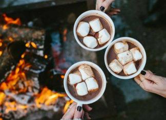 Trzy dłonie trzymające kubki z gorącą czekoladą i piankami