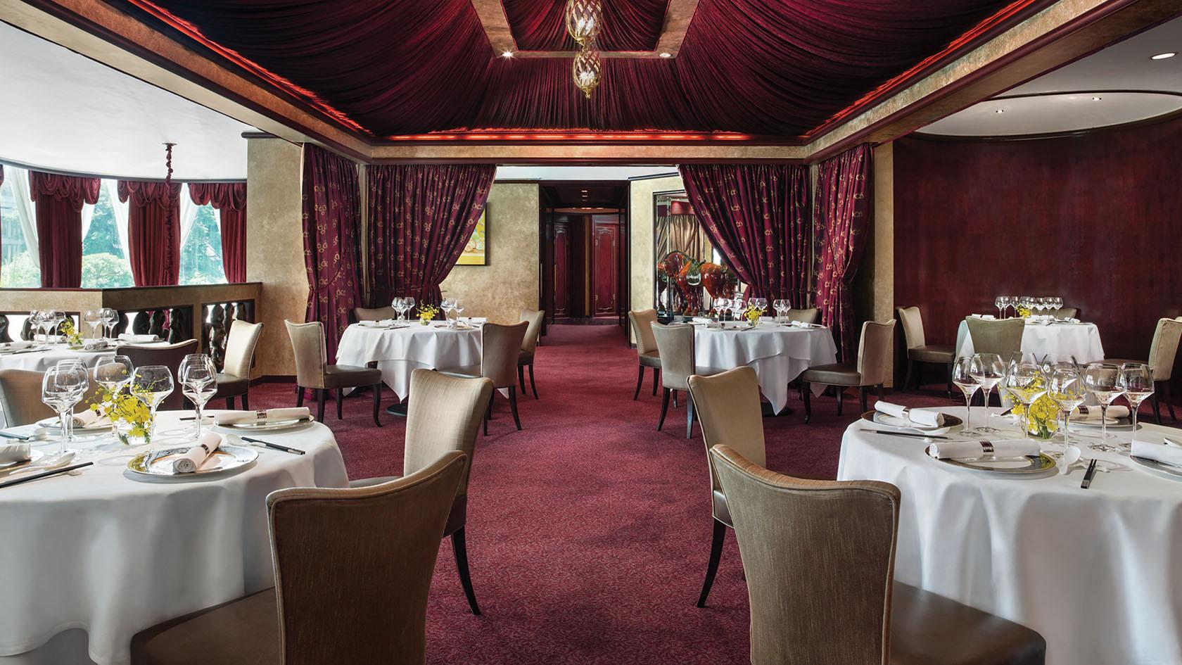 Wnętrze z bordowym dywanem, kremowymi krzesłami i białymi obrusami na stołach