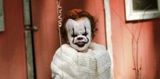 Dziecko przebrane za klauna trzyma czerwony balon i uśmiecha się szeroko.