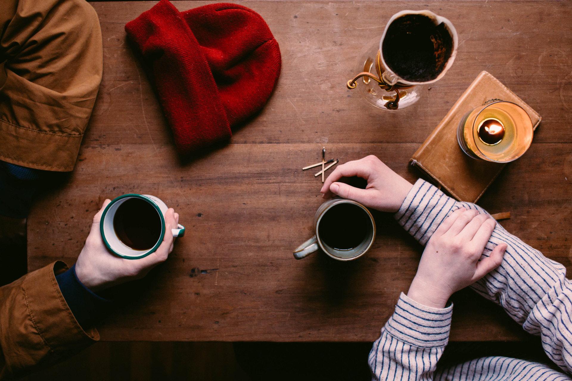 Widok na stół z kawą, czapką i dłońmi dwóch osób
