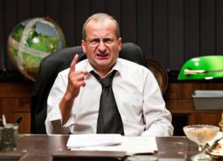 Mężczyzna siedzący za biurkiem w białej koszuli i czarnym krawacie, grożący palcem