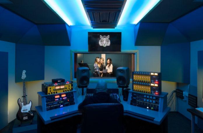 Studio muzyczne z niebieskmi światłami, za szybą trzy wokalistki