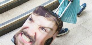 Walizka na kółkach z wyszczerzoną męską twarzą na pokrowcu