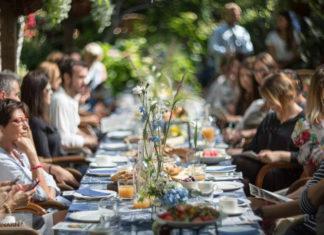 Zdjęcie ludzi siedzących w ogrodzie przy zastawionym stole