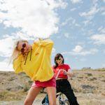 Dwie dziewczyny: Jedna w krótkiej spódniczce i żółtej bluzie, druga w czarnych spodniach i czerwonej koszulce, siedząca na rowerze