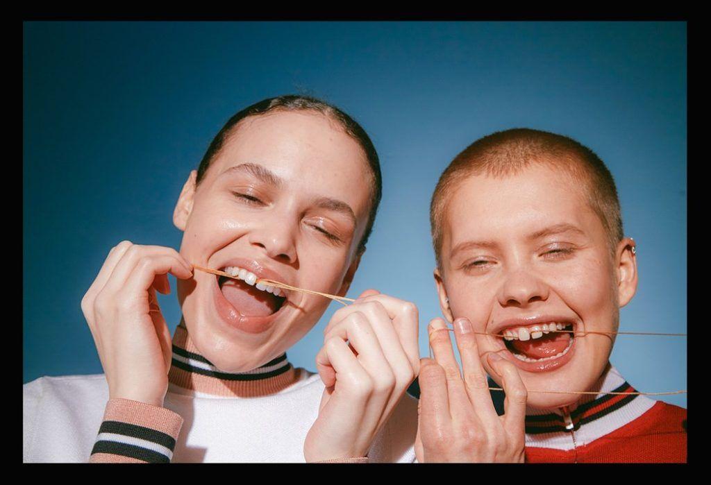 dwójka dzieci szeroko uśmiechających się, pokazujących przy tym swoją szparę między zębami, i czyszczące ją nitką dentystyczną