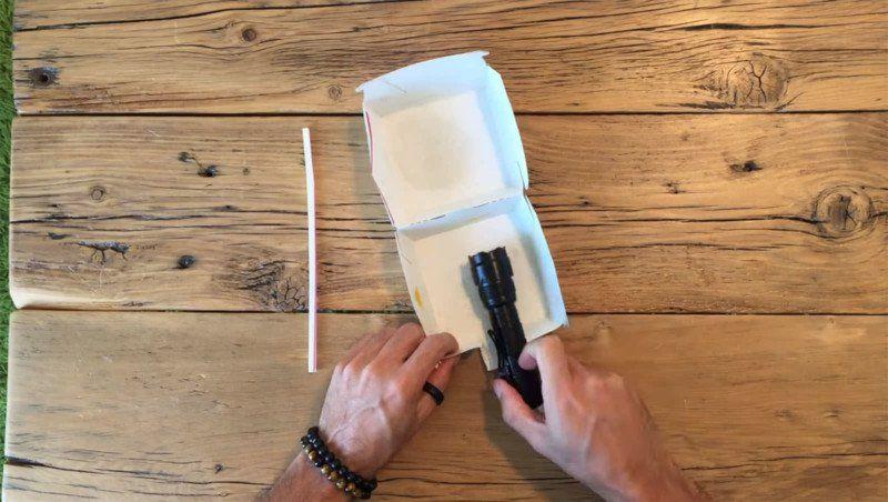Mężczyzna robi instalacje z latarki i pudełka.