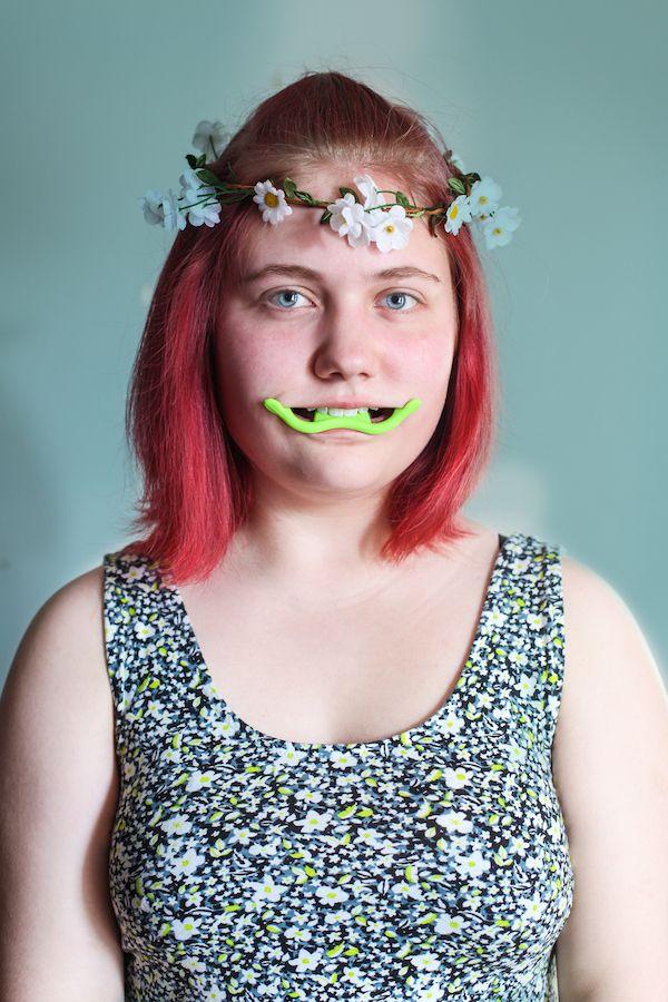 Dziewczyna w srebrnej sukience i wianku na głowie w z dziwnym zielonym urządzeniem w ustach