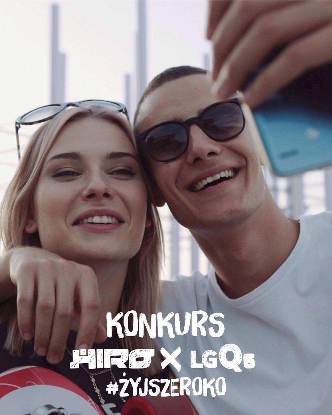 Uśmiechnięty chłopak i dziewczyna robiący sobie selfie